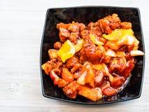 Porc en sauce aigre-doux dans la cuvette sur la table grise photographie stock