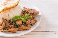porc fait sauter à feu vif avec le basilic sur le riz et l'oeuf au plat image libre de droits