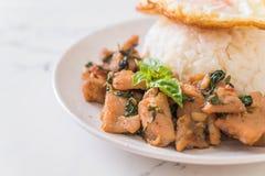 porc fait sauter à feu vif avec le basilic sur le riz et l'oeuf au plat photos stock