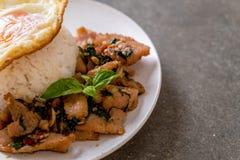 porc fait sauter à feu vif avec le basilic sur le riz et l'oeuf au plat photos libres de droits