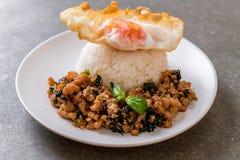 porc fait sauter à feu vif avec le basilic sur le riz et l'oeuf au plat image stock