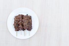 Porc grillé avec le bâton en bambou dans le plat blanc sur le fond en bois Images stock