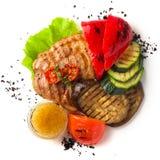 Porc grillé juteux avec des légumes sur un fond blanc, isolat photographie stock