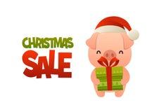Porc mignon heureux de bande dessinée avec le présent de cadeau et la vente de Noël des textes photographie stock libre de droits