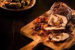 Porc rôti coupé en tranches avec le lard sur la planche à découper Images libres de droits