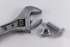 Porca e parafuso de prata da chave inglesa no branco Foto de Stock Royalty Free