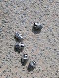 Porcas da roda de carro na estrada asfaltada Fotos de Stock