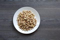 Porcas de pistache na placa branca Fotografia de Stock