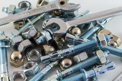 Porcas - e - aço dos parafusos e da chave de chave inglesa no fundo branco Fotografia de Stock Royalty Free
