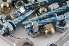 Porcas - e - aço dos parafusos e da chave de chave inglesa no fundo branco Imagens de Stock