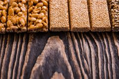 Porcas no caramelo, mel, porcas do esmalte do açúcar, sementes, sementes de linho em um fundo de madeira escuro da textura Alimen fotografia de stock