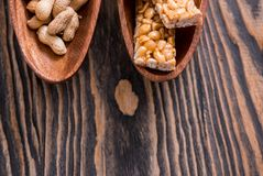 Porcas no caramelo, mel, porcas do esmalte do açúcar, sementes, sementes de linho em um fundo de madeira escuro da textura Alimen Foto de Stock