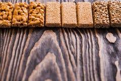 Porcas no caramelo, mel, porcas do esmalte do açúcar, sementes, sementes de linho em um fundo de madeira escuro da textura Alimen Imagem de Stock Royalty Free