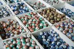 Porcelain Beads. Arrayed boxes containing different types of porcelain beads. Narrow DoF Stock Images