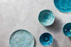 Porcelain blue bowls and plates on a gray marble table. Multi-colored ceramic vintage handmade dishes. Clay handcraft empty blue plates, bowls, covered with Royalty Free Stock Photo