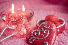 Porcelain box, lolipops and candles in the form of hearts on a pink background. Romantic concept of Valentines Day. Tinted photo. Stock Images