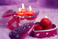 Porcelain box, lolipops and candles in the form of hearts on a pink background. Romantic concept of Valentines Day. Tinted photo. Stock Photo