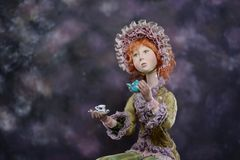 Porcelain clay ginger girl vintage dress bonnet tea. Porcelain paper mache clay. Statuette girl pretty woman young girl dress redhead beauty handmade handcrafted Royalty Free Stock Photography