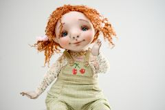 Porcelain clay young smiling redhead girl. Porcelain paper mache clay statuette girl pretty woman young girl smiling cheer smile redhead beauty overalls handmade Royalty Free Stock Image