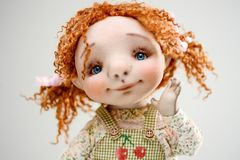 Porcelain clay young smiling redhead girl. Porcelain paper mache clay statuette girl pretty woman young girl smiling cheer smile redhead beauty overalls handmade Stock Photography