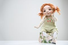 Porcelain clay young smiling redhead girl. Porcelain paper mache clay statuette girl pretty woman young girl smiling cheer smile redhead beauty overalls handmade Stock Images