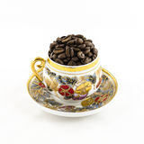 Porcelain coffee cup filled with coffee beans isolated on white Stock Photo