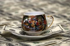 Porcelain coffee cup & money. The porcelain with Chinese picture coffee cup on the table-cloth from papery USA money, feng shui Stock Photos