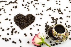 Porcelain coffee cup with rose flower and coffee beans heart Royalty Free Stock Photo