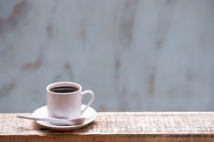 Porcelain coffee cup with spoon and saucer against a rustic background with copy space.  Stock Images