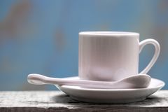 Porcelain coffee cup with spoon and saucer against a rustic background with copy space.  Royalty Free Stock Image