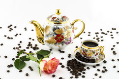 Porcelain coffee set (cup and jug) with rose flower and coffee beans Royalty Free Stock Photography