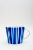 Porcelain cup. White porcelain cup with blue stripes view from 0 degrees angle Stock Image