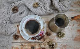 Porcelain cup of black coffee and coffeepot on the rustic background with winter decoration. Stock Image