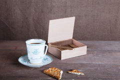 Porcelain cup of coffee, a box of cigarillos and cookies on old Stock Photography
