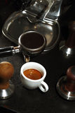 Porcelain cup of coffee and portafilter of an espresso machine Stock Photo