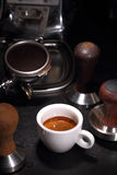 Porcelain cup of coffee and portafilter of an espresso machine Royalty Free Stock Photo