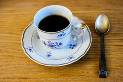 Porcelain cup with coffee and a silver spoon Stock Photos