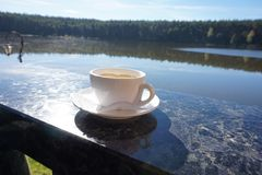 A porcelain cup of coffee that sits on the side of the balcony, with a magical view of the lake. stock image