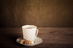 Porcelain cup of coffee with toffee on old wooden table against Royalty Free Stock Images