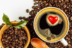 Porcelain cup of hot coffee. Roasted coffee beans. Heart symbol. Food trading. Fair trade coffee. Food photography. Porcelain cup of hot coffee. Roasted coffee royalty free stock image