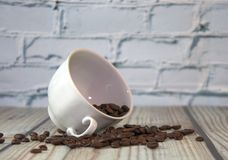 A porcelain cup lies on its side in a pile of coffee beans, a wooden table against a white brick wall. Close-up. A porcelain cup lies on its side in a pile of stock photography