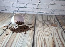 A porcelain cup lies on its side in a pile of coffee beans, a wooden table against a white brick wall. Close-up. A porcelain cup lies on its side in a pile of royalty free stock photo