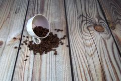 A porcelain cup lies on its side in a pile of coffee beans, a wooden table against a white brick wall. Close-up. A porcelain cup lies on its side in a pile of stock photos