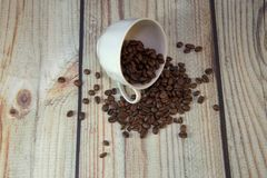 A porcelain cup lies on its side in a pile of coffee beans, a wooden table against a white brick wall. Close-up. A porcelain cup lies on its side in a pile of royalty free stock image