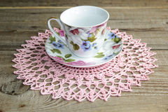 Porcelain cup. With openwork napkin on wooden table Royalty Free Stock Photos
