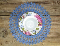 Porcelain cup. With openwork napkin on wooden table Royalty Free Stock Images