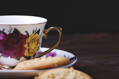 Porcelain cup with pretty ornaments next to some cookies on wooden table. Food and drink Stock Images