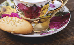 Porcelain cup with pretty ornaments next to some cookies on wooden table. Food and drink Royalty Free Stock Image