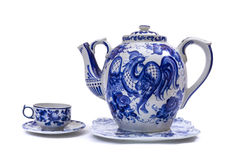 Porcelain teapot, cup and saucer in folk style painted blue on white background. Crockery in russian folk style royalty free stock photography