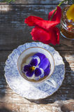 Porcelain cup of tea and beautiful spring flowers in vase on a wooden table in the garden. Summer party. Royalty Free Stock Image